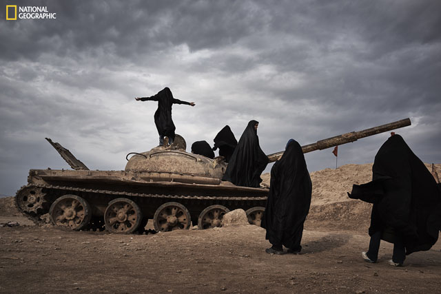 There are relics left along the Iran-Iraq boarders. A group of Iranian female students play around an abandoned tank. Among them, one girl stands on the tank with her arms open.